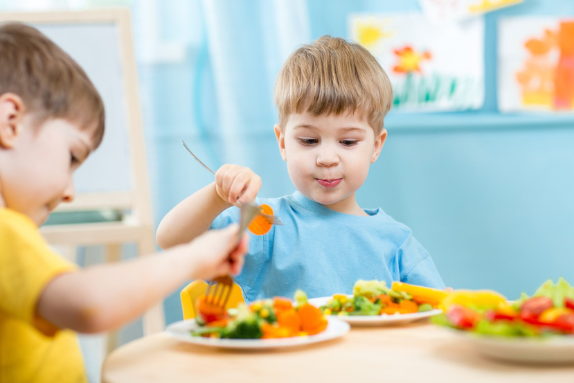 two preschool aged boys eating at a table