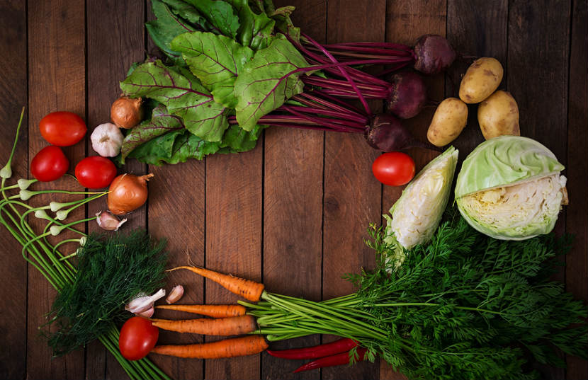 produce like carrots, cabbage, potatoes, tomatoes, garlic and onion on a wooden floor