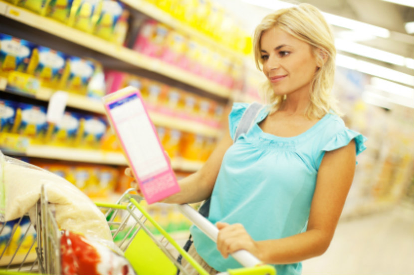 woman reading nutrition label at grocery store
