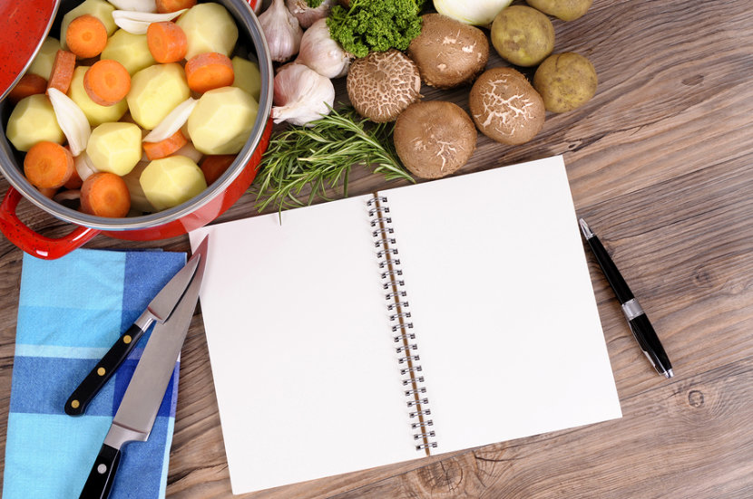 notebook in a kitchen with pots of carrots and potatoes, mushrooms and garlic