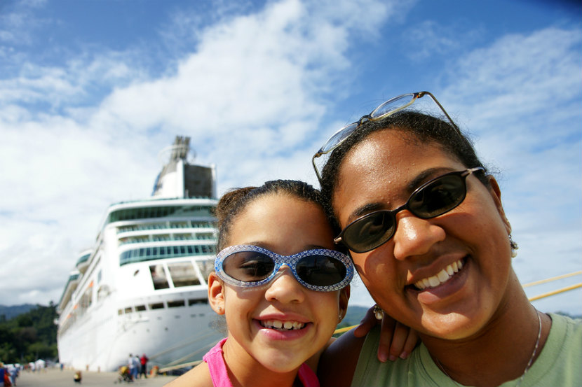 a mom and her daughter standing in front of a cruise ship