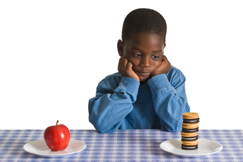 boy deciding between healthy food and dessert