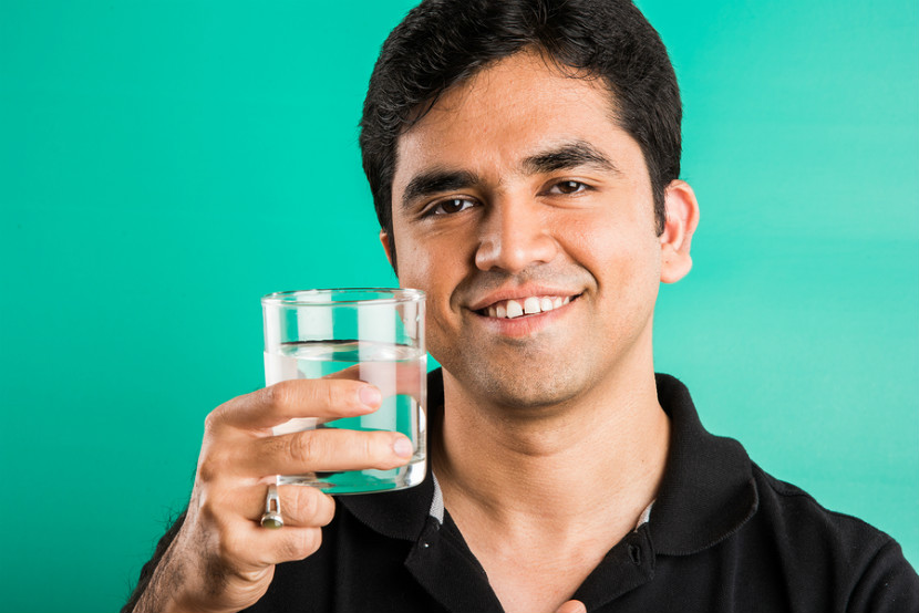 man drinking a glass of water
