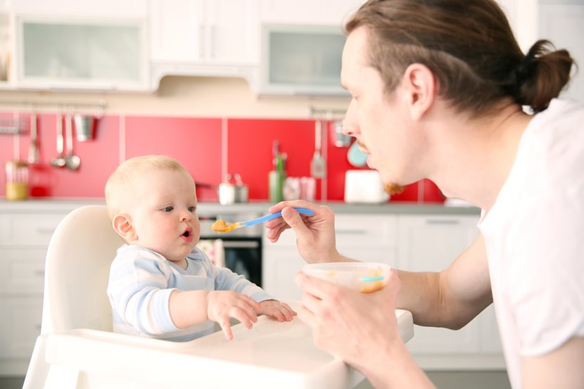 father feeding solid foods to his baby