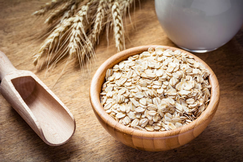 wooden bowl with oats in it with wheat on the table