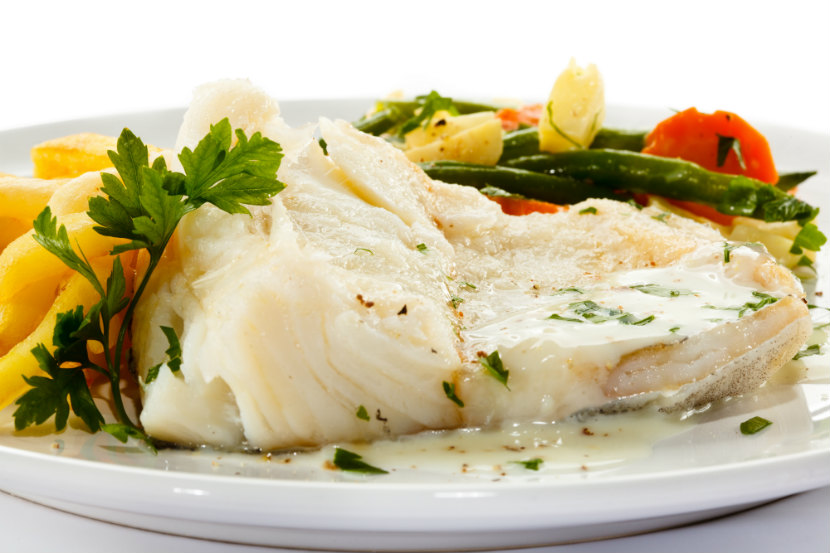 grilled white fish on a plate with vegetables
