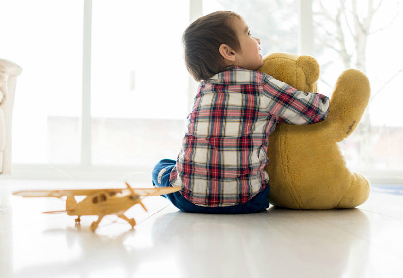 child sitting on the ground with toys