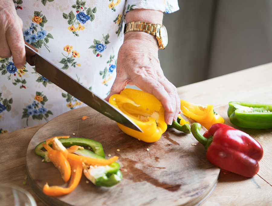 elderly woman slicing up a bell pepper in the kitchen