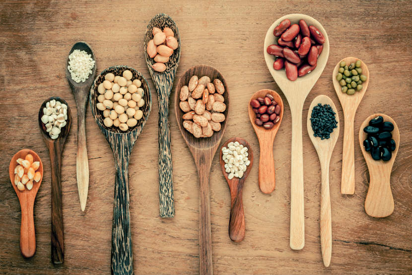 wooden spoons with various legumes on them