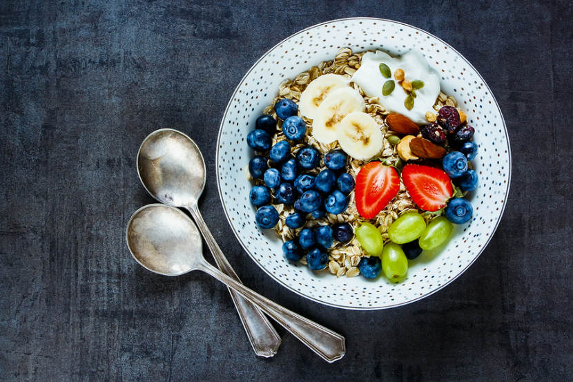 bowl of oats with fruit, nuts, seeds and yogurt on top