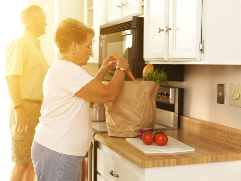 senior couple unloading groceries in their kitchen