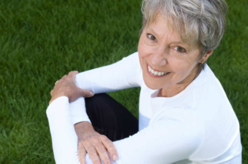 happy senior woman sitting on grass