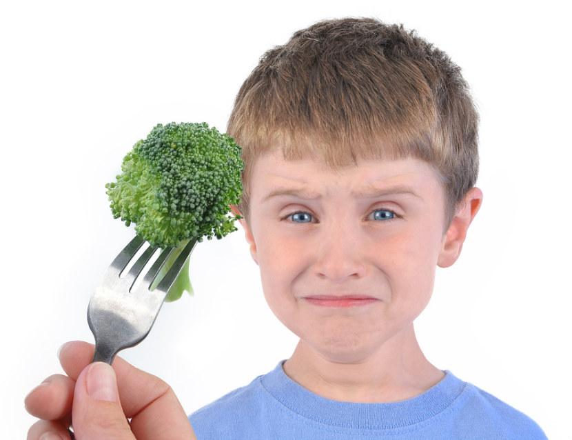 入學年齡的男孩看起來不高興吃西蘭花