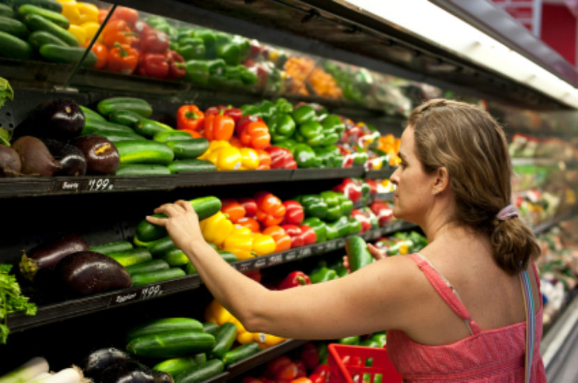 women in the produce section of the grocery store