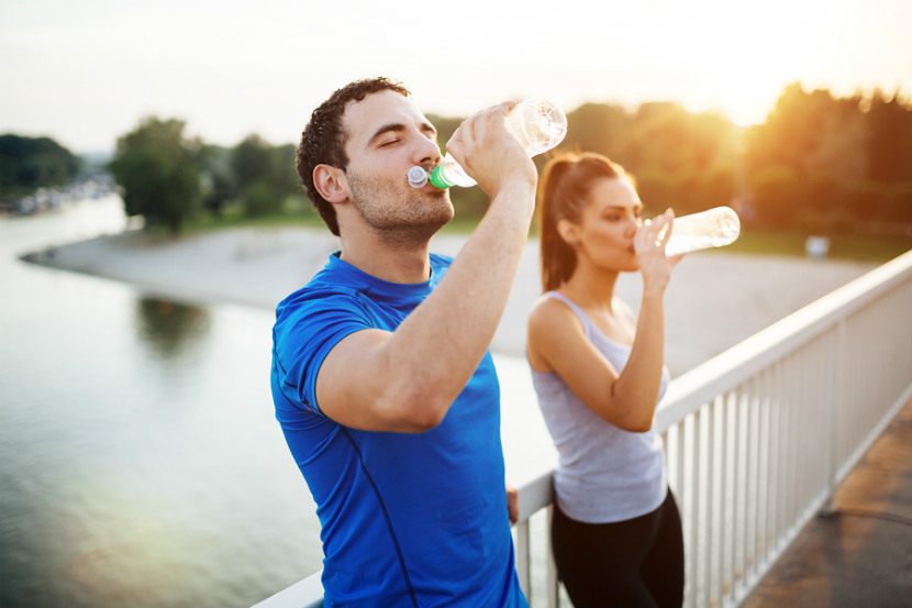 woman and man drinking bottles of water