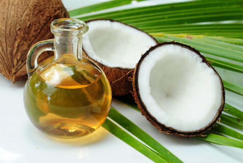 bottle of coconut oil beside a coconut