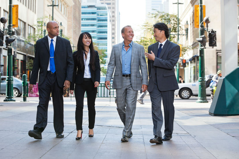 men and women walking in business suits