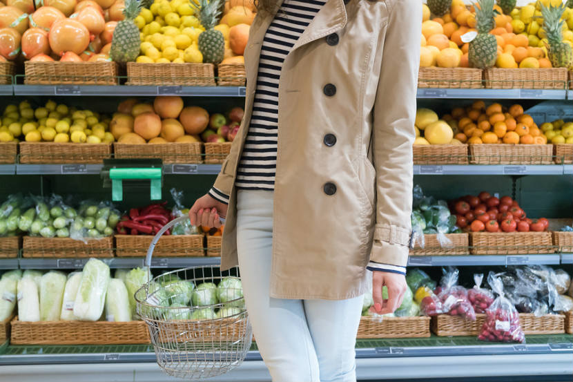 woman shopping in produce section of grocery store