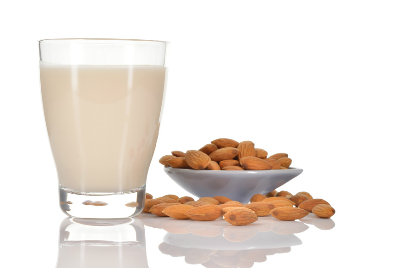 glass of almond milk with some almonds on a table