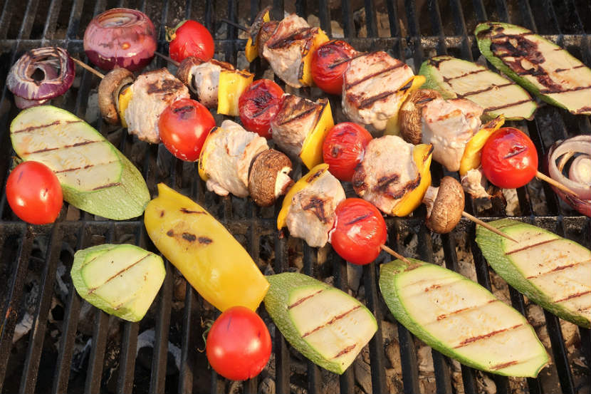 meat and vegetable kebabs being cooked on a bbq