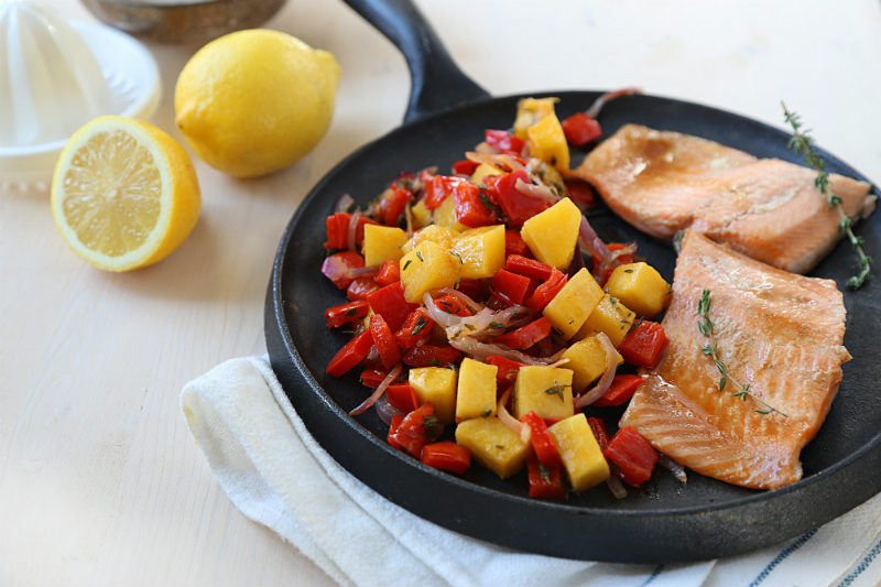 glazed trout and roasted vegetables on a skillet