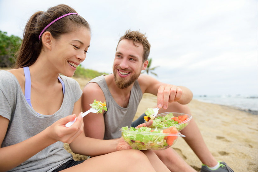 young man and young woman outside eating a salad
