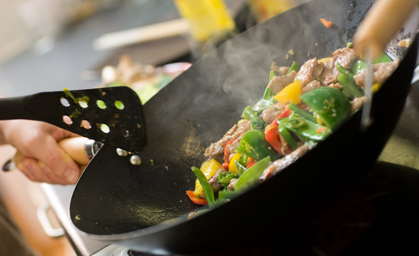beef and vegetable stir fry being cooked in a wok