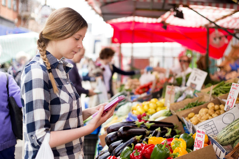 woman looking at list while shopping for fruit and vegetables
